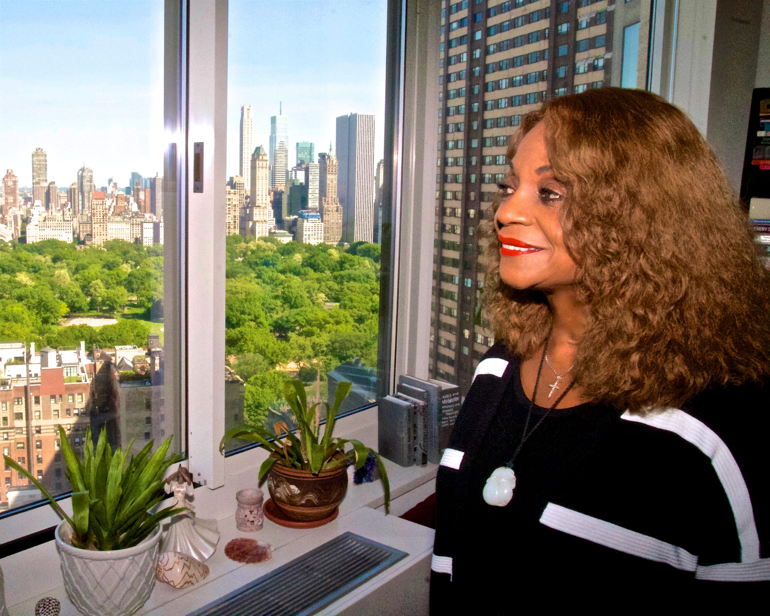 Eugenia Foxworth looking out a window at New York City Skyline
